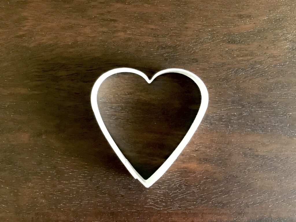 heart cookie cutter on dark wood background