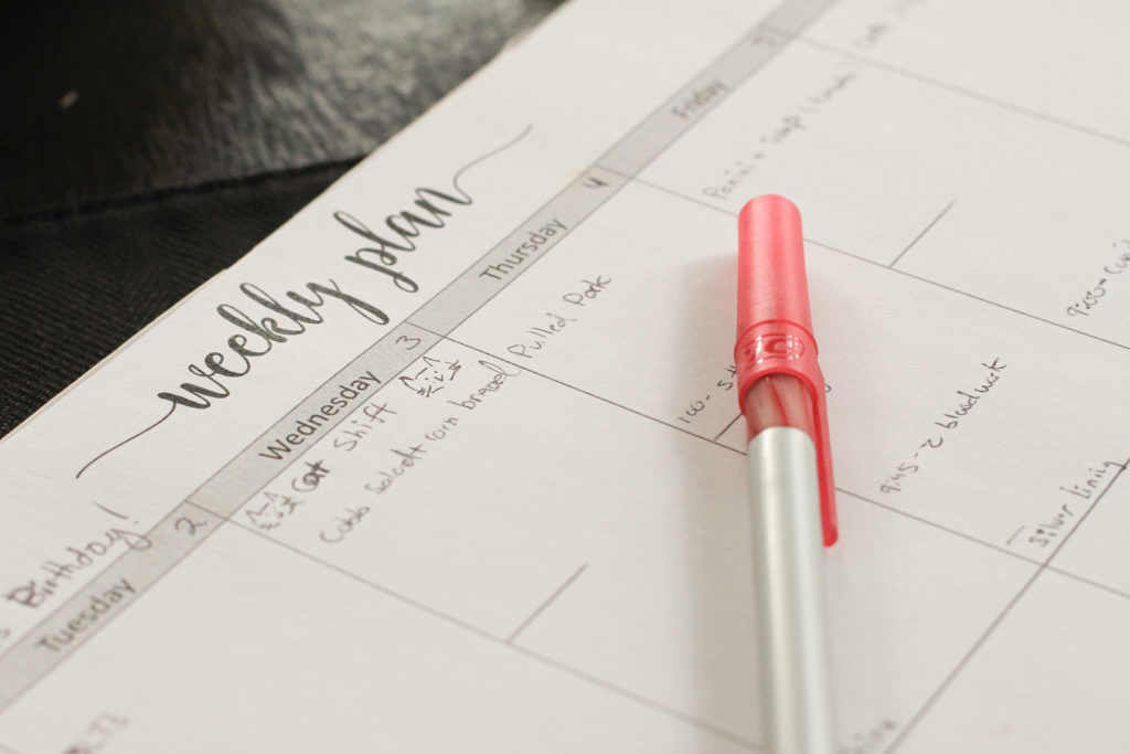 Weekly planner with red pen.