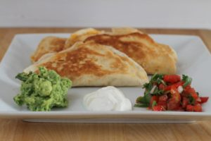 Two quesadillas on a white plate with guacamole and salsa.