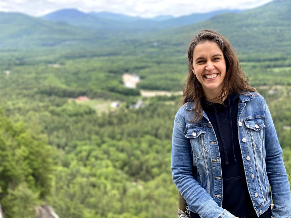 Kristen in front of a mountainous scene with green trees.