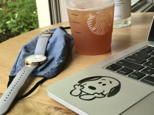 A laptop, watch, and iced tea on a Starbucks table.