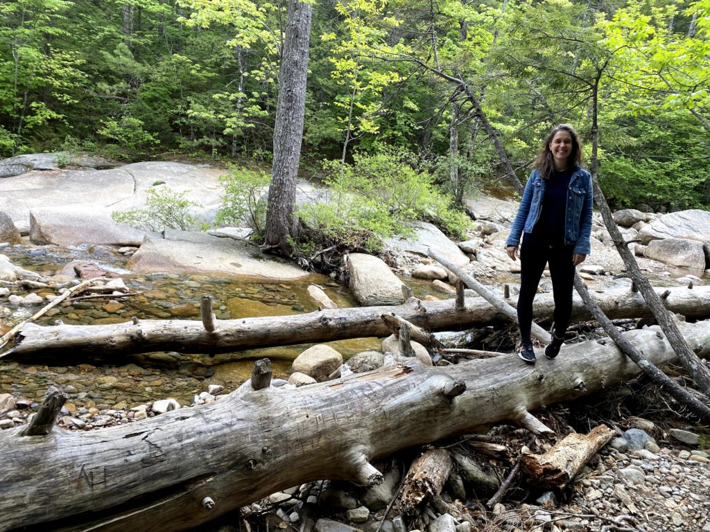 Kristen standing on a log in the woods.