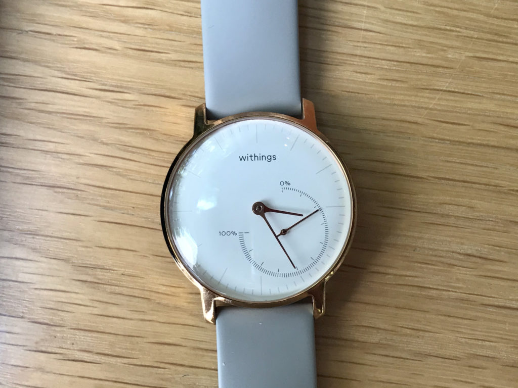 A watch with a white face, gold hardware, and a gray band.
